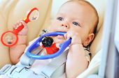 stock photo of teething baby  - baby laying in bouncer chair with toys - JPG