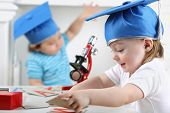 Happy little girl in blue graduation hat lays out cards with letters on table beside boy with microscope