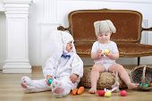 Little boy in costumes bunny and girl in knitted hat with hare ears sitting on floor with Easter eggs