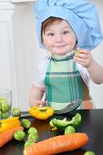 Beautiful little girl in kitchen apron and cap play at table with vegetables