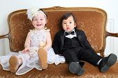 Laughing little girl in beautiful white dress and serious boy in black suit sitting on couch