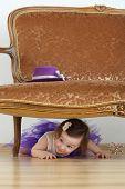 Beautiful little girl in purple skirt lying on floor under sofa