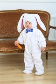 Little boy in costume bunny holding carrot