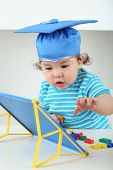 Small boy in blue graduation hat sitting at table with children magnetic board with colored letters