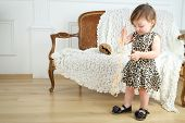 Beautiful little girl in leopard print dress with beads stands near sofa in room
