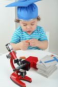 Small boy in blue graduation hat sitting at table with red microscope
