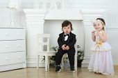 Beautiful little girl in white long dress plays with small boy in black tuxedo
