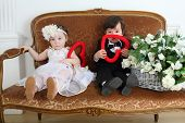 Beautiful little kids in costumes bride and groom sitting on couch with hearts