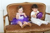Beautiful little children in white and purple costumes sitting on couch