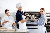 Portrait of smiling female chef passing baking sheet to male colleague by oven in commercial kitchen