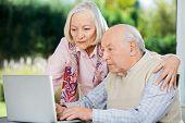 Serious senior man and woman using laptop at nursing home