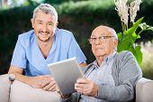 Portrait of smiling male caretaker and senior man holding digital tablet at nursing home porch