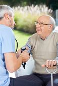 Male doctor measuring blood pressure of elderly man at nursing home