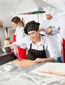 Portrait of smiling female chef cutting ravioli pasta at counter with colleagues working in background at commercial kitchen