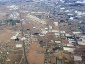 An image shot from an airplane shows an industrial expanse lined with residential tracts of homes.