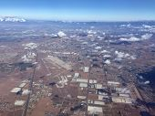 An image shot from an airplane shows a small landing strip surrounded by industrial buildings and residential tracts of homes.
