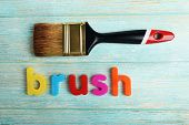 Brush word formed with colorful letters on wooden background