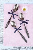 Metal spoons and chamomile on pink napkin on wooden background