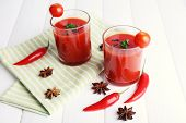 Tomato juice in glasses and fresh vegetables on napkin on light wooden background
