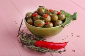 Green olives in oil with spices and rosemary in bowl on wooden table