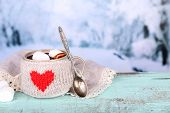 Cup of tasty hot cocoa, on wooden table, on light background
