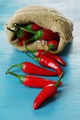 Red hot chili peppers in sack on wooden background