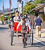 KYOTO, JAPAN-OCT 24,2014: Jinrikisha driven by an unidentified driver carrying two  tourists in Kyoto on Oct 24, 2014, ,Japan.The word jinrikisha is of Japanese origin and means human-powered vehicle.