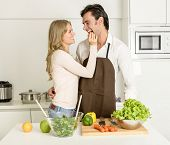 Happy couple fooling around while preparing healthy dinner