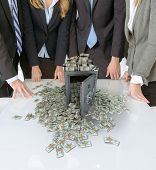 businesspeople around a table with a safe and piles of cash
