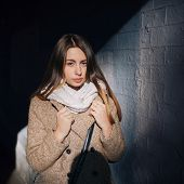 Street portrait of a handsome young girl in coat