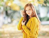 Autumn portrait of a young beautiful redhead woman in yellow sweater