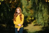 Autumn portrait of a young beautifu redhead woman in yellow sweater with a noon sun and shallow dept