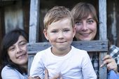 Portrait of little boy with his mother and older sister in background, outdoors in countryside.