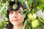 Young cute girl in the apple orchard, closeup portrait.