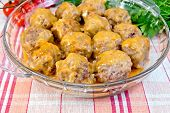 Meatballs with sauce in glass pan on linen tablecloth