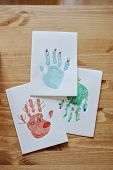 Kids handprints Christmas post cards on white paper