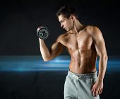 sport, bodybuilding, training and people concept - young man with dumbbell flexing biceps over dark background