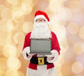 christmas, advertisement, technology, and people concept - man in costume of santa claus with laptop computer over beige lights background