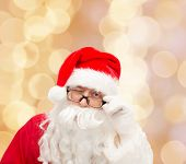 christmas, holidays and people concept - close up of santa claus in glasses winking over beige lights background