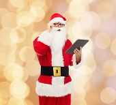 christmas, holidays, technology and people concept - man in costume of santa claus with tablet pc computer over beige lights background