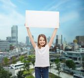 advertisement, childhood, happiness and people concept - smiling little child in white t-shirt holding blank board over city background