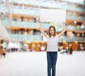 advertisement, childhood, sale and people concept - smiling little child in white t-shirt holding blank board over shopping center background