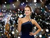 shopping, wealth, holidays and people concept  - smiling woman in evening dress holding credit card over snowy night city background