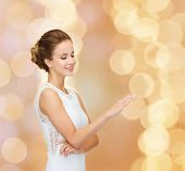 engagement, celebration, wedding and people concept - smiling woman in white dress wearing diamond ring over beige lights background