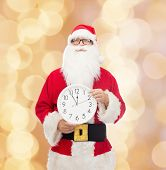 christmas, holidays and people concept - man in costume of santa claus with clock showing twelve pointing finger over beige lights background