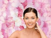beauty, people and health concept - smiling young woman with bare shoulders over pink lights background