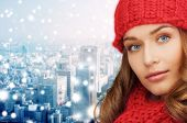 happiness, winter holidays, christmas and people concept - close up of young woman in red hat and scarf over blue snowy background