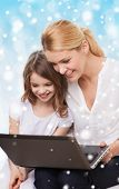 family, childhood, holidays, technology and people concept - smiling mother and little girl with laptop computer over blue background with snow