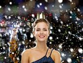 people, holidays, royalty and christmas concept - smiling woman in evening dress wearing golden crown over snowy night city background