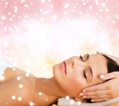 beauty, health, holidays, people and spa concept - beautiful woman in spa salon getting face or head massage over pink background